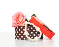 Pearls inside open gift box with pink rose. On white background Royalty Free Stock Images