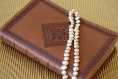 Pearls on leather. Pearls on a leather bound cover with patterns Royalty Free Stock Photos