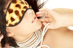 Pearls and leopard mask. Lovely brunette with pearls in leopard mask Stock Images