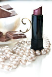Pearls and lipstcks. Dark lipstick and white pearl necklace in the foreground, and pieces of chocolate in a coffee cup out of focus in the background Royalty Free Stock Photo