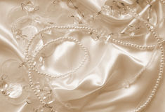 Pearls and nacreous beeds on silk as wedding background. In Sepi Royalty Free Stock Image