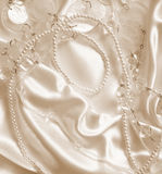Pearls and nacreous beeds on silk as wedding background. In Sepi Royalty Free Stock Photography