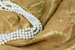 Pearls Necklace. On gold silk Stock Image
