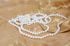 Pearls necklace. Woman white  pearls necklace on gold silk Royalty Free Stock Photos
