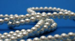 Pearls necklace on blue Royalty Free Stock Photos