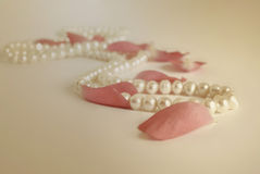 Pearls necklace and rose petals vintage background Royalty Free Stock Image