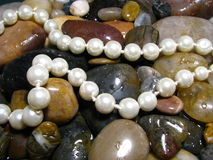 Pearls over river rocks Royalty Free Stock Photo