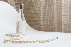 Pearls and Perfume. Women's perfume and pearl necklace Royalty Free Stock Photography