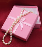 Pearls at pink box. White pearls at pink box on wine-colored textile Royalty Free Stock Photography