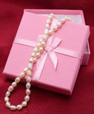 Pearls at pink box. White pearls at pink box on wine-colored textile Stock Photography