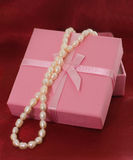 Pearls at pink box. White pearls at pink box on wine-colored textile Royalty Free Stock Photos