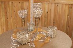 Pearls and Prisms. Table set with candle holders of differing shapes, sizes and heights, made of round crystals set in metal. A string of pearls and vibrant stock image