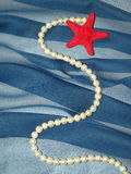 Pearls and red star on blue fabric. Natural pearls and red sea star on the blue fabric Stock Images