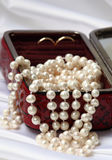 Pearls and rings in red jewelry box Royalty Free Stock Photography