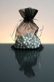 Pearls in sack. Pearls in black sack with ribbon on glass floor Royalty Free Stock Photo