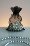 Pearls in sack and pearl necklace. Pearls in black sack and pearl necklace in front with light background Stock Photography