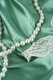 Pearls and Satin. White pearls and green satin with lace trim Royalty Free Stock Photo