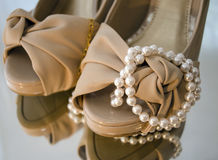 Pearls and shoes. A pearl string wrapped around a pair of shoes Royalty Free Stock Photography
