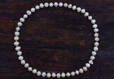 Pearls string circle shaped top view old wood Stock Photo
