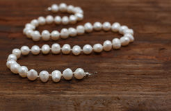 Pearls string wooden table closeup Royalty Free Stock Images