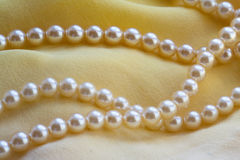 Pearls threads on a yellow fabric. Stock Photo