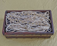 Pearls in vintage wooden crib Stock Photos