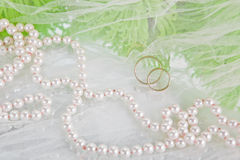 Pearls, wedding rings and bouquet. White necklace of pearls, wedding rings and bouquet of chrysanthemums on a white veil Royalty Free Stock Images
