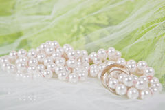 Pearls, wedding rings and bouquet. White necklace of pearls, wedding rings and bouquet of chrysanthemums on a white veil Stock Image