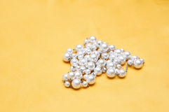 Pearls on yellow satin Stock Image