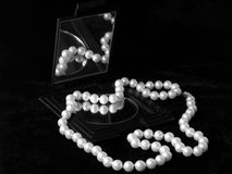 Pearly Reflection. Strand of pearls reflected in mirror, black and white royalty free stock image