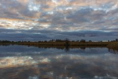 The pearly sky colors the broken clouds beautifully at lake Zoetermeerse plas in Zoetermeer, Netherlands royalty free stock photography