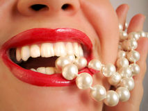 Pearly white teeth. Glamorous lips and pearly white teeth biting down on a pearl necklace Stock Images