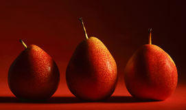 Pears #1. Three forelle pears on a gradated red background Royalty Free Stock Images