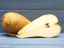 Pears. One and a half pears with a blue wooden background Stock Images