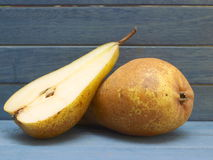 Pears. One and a half pears with a blue wooden background Royalty Free Stock Images