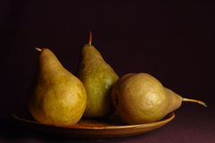 Pears. Three pears on plate on black background Royalty Free Stock Photography