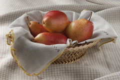 Pears. Some red pears in the wicker on the tablecloth Royalty Free Stock Image