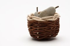 Pears. Made from pebbles and brown wicker basket Royalty Free Stock Photos