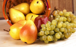 Pears, apple and grapes on the table royalty free stock image