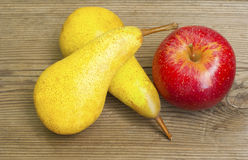 Pears, apple on old wooden table Royalty Free Stock Photos
