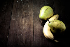 Pears, bananas on an old wooden table background Royalty Free Stock Photography
