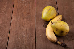 Pears, bananas on an old wooden table background Stock Photography