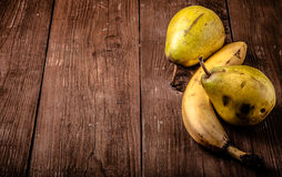 Pears, bananas on an old wooden table background. tinted Royalty Free Stock Image