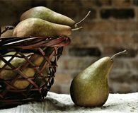 Pears in a basket. Studio shot of ripe pears in a woodwn basket against a brick wall Royalty Free Stock Photos