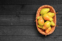 Pears in a basket on wooden background Royalty Free Stock Photography