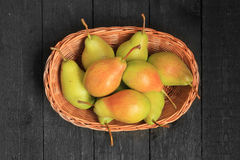 Pears in a basket on wooden background Stock Photo