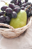 Pears and black grapes in the basket Stock Photo
