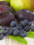 Pears with blueberries and plums Stock Images