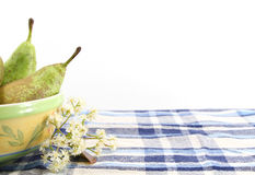 Pears in a bowl, white flowers, space for text. Some pears in a bowl of ceramic over a blue checkered tablecloth, space for text on top, landscape cut Royalty Free Stock Photography