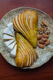 Pears, camembert and nuts. Appetizer for wine. Fruit, cheese, walnut and almond Royalty Free Stock Image